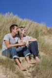 Pares românticos do homem & da mulher que sentam-se na praia Foto de Stock Royalty Free