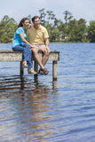Pares românticos do homem e da mulher que sentam-se por Lago Foto de Stock Royalty Free