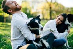 Pares românticos em cães de passeio do amor na natureza e no sorriso Imagens de Stock Royalty Free