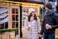 Pares românticos felizes que guardam as mãos ao andar junto em uma rua decorada no tempo do Natal fotografia de stock royalty free