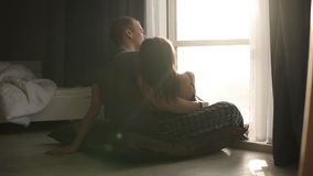 Pares românticos na roupa doméstica que senta-se no assoalho na manhã Mulher e homem caucasianos adultos novos bonitos video estoque