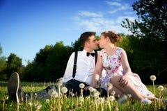 Pares românticos no amor aproximadamente para beijar o assento na grama Fotos de Stock Royalty Free