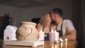 Pares românticos no amor que trabalha junto na oficina do estúdio do ofício e para tirar um coração em um potenciômetro de argila filme