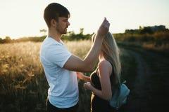 Pares românticos no por do sol Dois povos no amor no por do sol ou no nascer do sol Homem e mulher no campo Foto de Stock Royalty Free