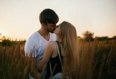 Pares românticos no por do sol Dois povos no amor no por do sol ou no nascer do sol Homem e mulher no campo Fotografia de Stock Royalty Free