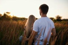 Pares românticos no por do sol Dois povos no amor no por do sol ou no nascer do sol Homem e mulher no campo Foto de Stock