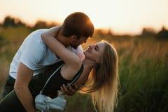 Pares românticos no por do sol Dois povos no amor no por do sol ou no nascer do sol Homem e mulher no campo Fotos de Stock Royalty Free