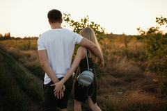 Pares românticos no por do sol Dois povos no amor no por do sol ou no nascer do sol Homem e mulher no campo Imagem de Stock Royalty Free