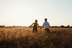 Pares românticos no por do sol Dois povos no amor no por do sol ou no nascer do sol Homem e mulher no campo Fotos de Stock