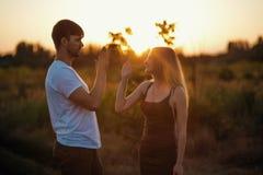 Pares românticos no por do sol Dois povos no amor no por do sol ou no nascer do sol Homem e mulher no campo Imagens de Stock