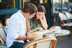 Pares românticos novos com o mapa no café francês Foto de Stock Royalty Free