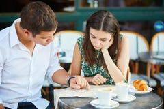 Pares românticos novos com o mapa no café francês Fotos de Stock
