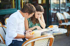Pares românticos novos em um café exterior acolhedor em Paris, França Fotografia de Stock Royalty Free