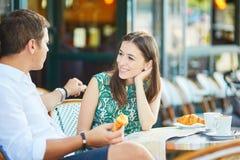 Pares românticos novos em um café exterior acolhedor em Paris, França Fotos de Stock