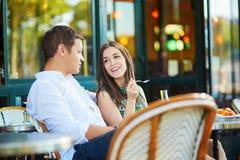 Pares românticos novos em um café exterior acolhedor em Paris, França Foto de Stock Royalty Free