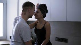 Pares românticos novos na cozinha A jovem mulher 'sexy' está sentando-se no counttable na roupa e na toalha de banho domésticas vídeos de arquivo