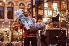 Pares românticos novos que apreciam passando o tempo junto no Natal na rua decorada com luzes bonitas feliz imagens de stock royalty free