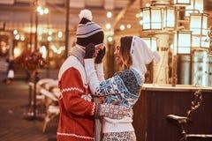 Pares românticos novos que têm o divertimento e que apreciam passando o tempo junto no Natal na rua decorada com bonito imagem de stock