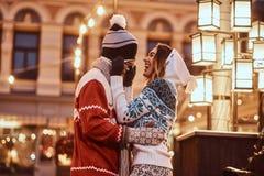 Pares românticos novos que têm o divertimento e que apreciam passando o tempo junto no Natal na rua decorada com bonito imagens de stock