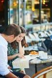 Pares românticos novos usando o mapa em um café exterior acolhedor em Paris, França Fotografia de Stock Royalty Free