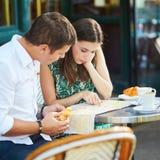 Pares românticos novos usando o mapa em um café exterior acolhedor em Paris, França Foto de Stock Royalty Free