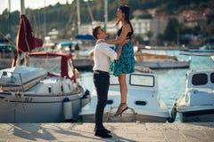 Pares românticos que abraçam na praia Tendo uma data romântica do divertimento Comemorando o aniversário Rosa vermelha fotos de stock