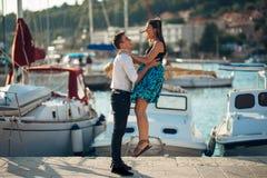 Pares românticos que abraçam na praia Tendo uma data romântica do divertimento Comemorando o aniversário Rosa vermelha imagens de stock