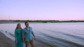 Pares românticos que andam ao longo de uma praia no por do sol vídeos de arquivo