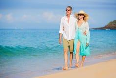 Pares românticos que andam na praia fotos de stock