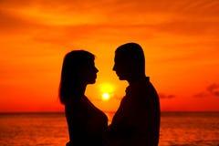 Pares românticos que beijam na praia tropical com por do sol no CCB Foto de Stock Royalty Free