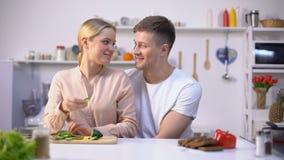 Pares românticos que cozinham a salada, lovingly abraçando, estilo de vida saudável feliz do vegetariano filme