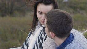 Pares românticos que descansam em uma rocha e em um sorriso lentamente video estoque