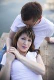 Pares românticos que descansam na ponte na costa do lago no por do sol Fotografia de Stock