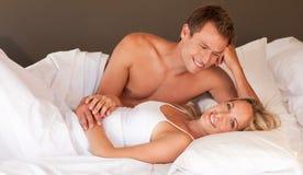 Pares românticos que encontram-se em uma cama Foto de Stock Royalty Free