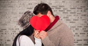 Pares românticos que escondem sua cara atrás do coração vermelho Imagens de Stock