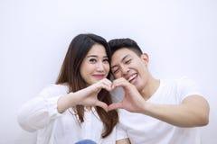 Pares românticos que fazem o símbolo do coração com mãos imagens de stock royalty free