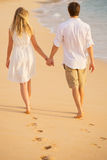 Pares românticos que guardam as mãos que andam na praia no por do sol Fotos de Stock Royalty Free