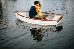 Pares românticos que sentam-se em um barco e em um beijo fotos de stock