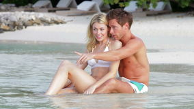 Pares românticos que sentam-se pela costa na praia Fotos de Stock Royalty Free