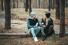 Pares românticos que sentam-se perto da fogueira, fundo da floresta do outono Mulher loura nova e homem considerável Imagem de Stock