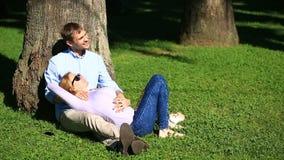 Pares românticos que sentam-se sob uma palmeira Uma menina no regaço de um indivíduo Um par loving que descansa em um parque na g filme