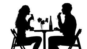 Pares românticos que têm o jantar, vidros do tinido video estoque