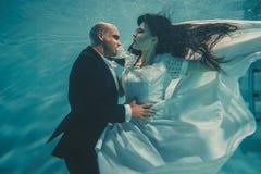 Pares rom?nticos bonitos de noivos ap?s o casamento que nadam delicadamente sob a ?gua e para relaxar foto de stock