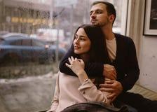 Pares rom?nticos El individuo de amor abraza a su novia hermosa que se sienta en el alf?izar en un caf? acogedor imagen de archivo