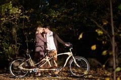 Pares rom?nticos, hombre y cierre atractivo de la muchacha junto en la bicicleta en t?ndem en parque oscuro del oto?o imagenes de archivo