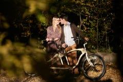 Pares rom?nticos, hombre y cierre atractivo de la muchacha junto en la bicicleta en t?ndem en parque oscuro del oto?o foto de archivo