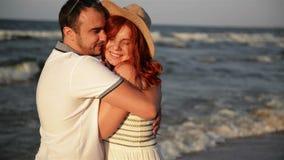 Pares rom?nticos que se besan y que abrazan en la playa durante puesta del sol Colores asoleados suaves See est? en el fondo metrajes