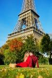 Pares rom?nticos que tienen comida campestre en la hierba cerca de la torre Eiffel fotografía de archivo libre de regalías