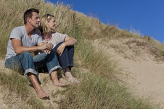 Pares románticos que se sientan junto en una playa Imagenes de archivo