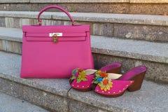 Pares rosados de neón brillantes de zapatos del ` s de las mujeres con el bolso en escaleras de mármol Imagen de archivo